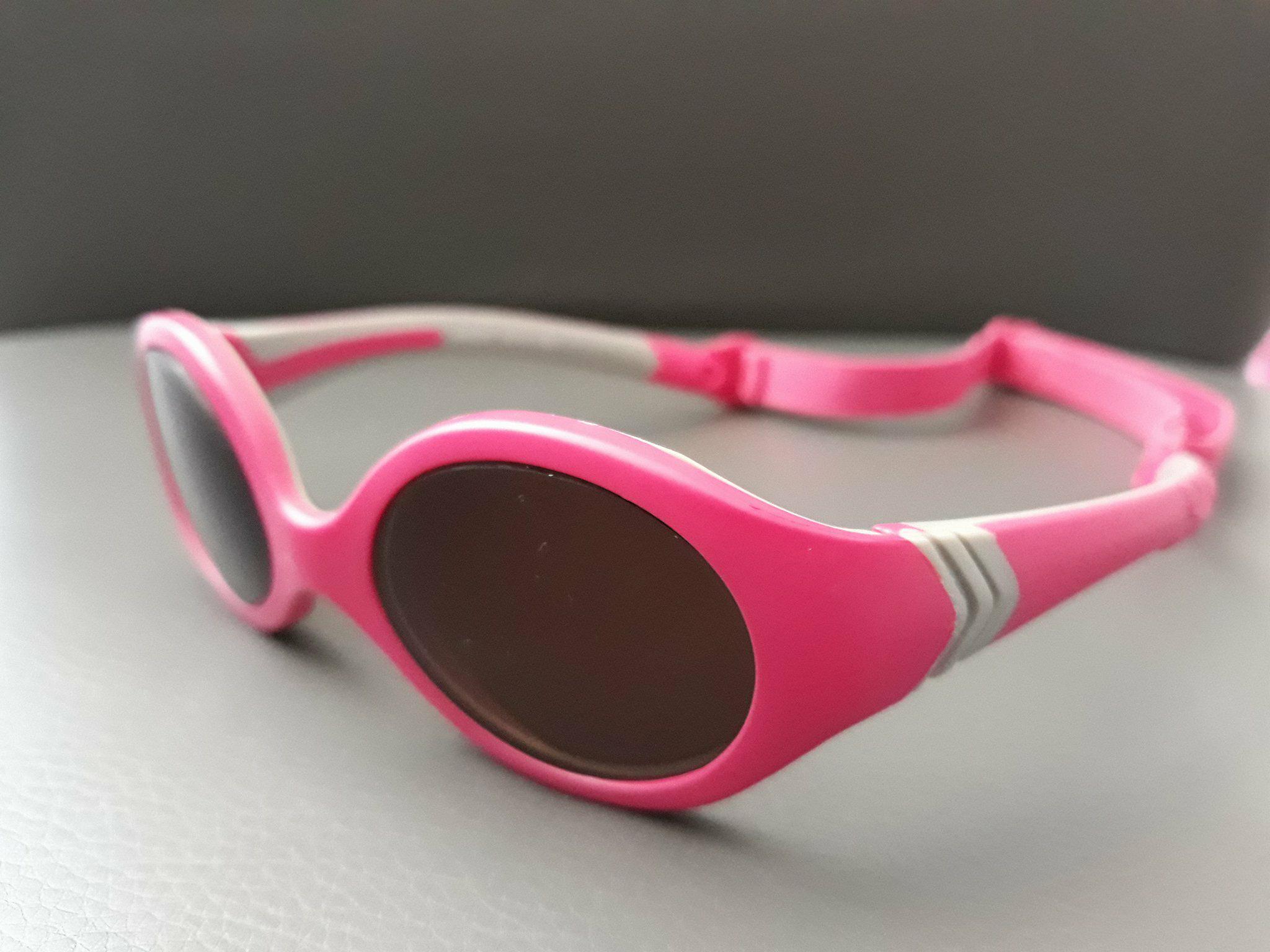 Okulary przeciwsłoneczne dla niemowląt zregulowaną gumką wkolorze różowym.