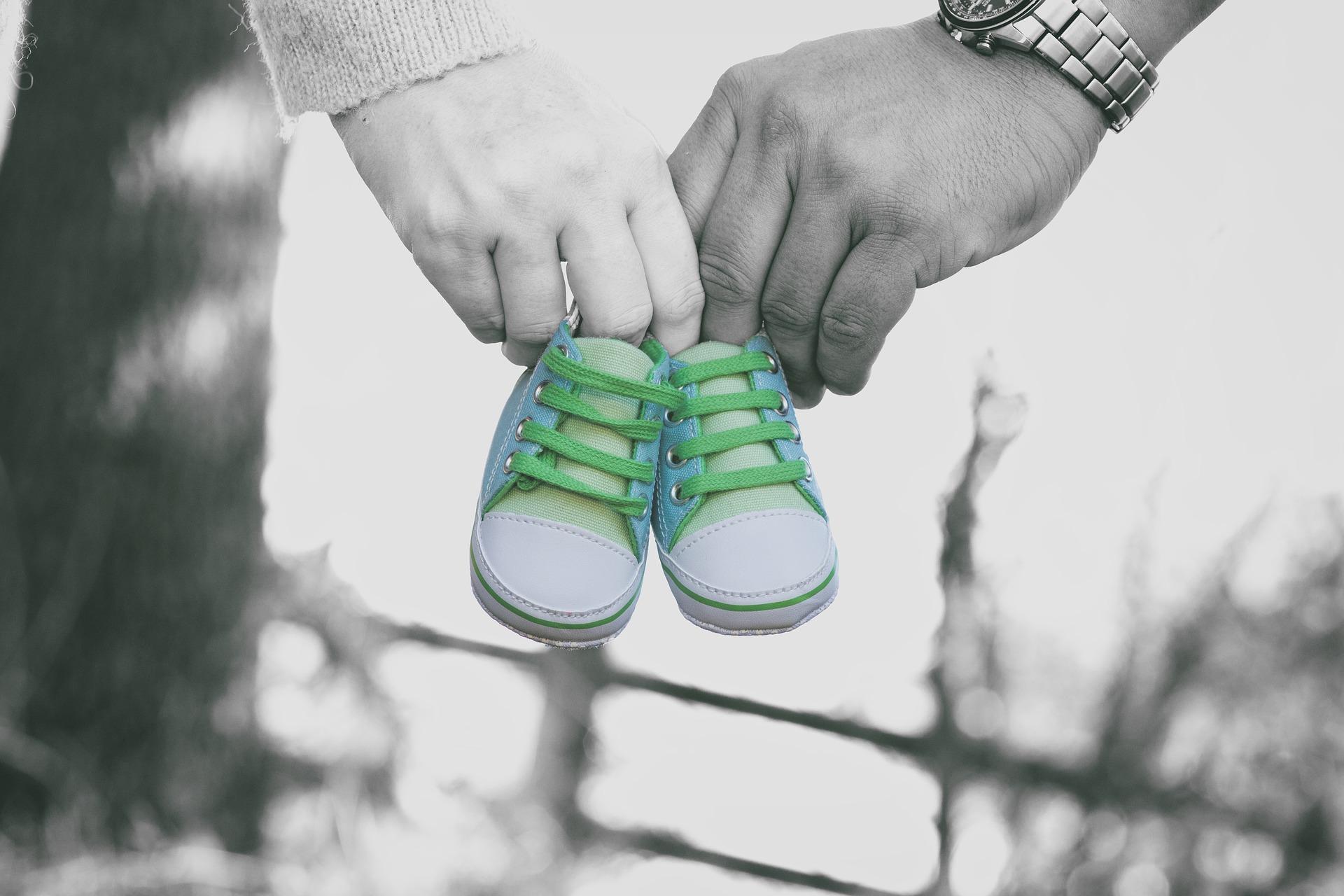 Para trzymająca buciki niemowlęce, które mówią jestem w ciąży.