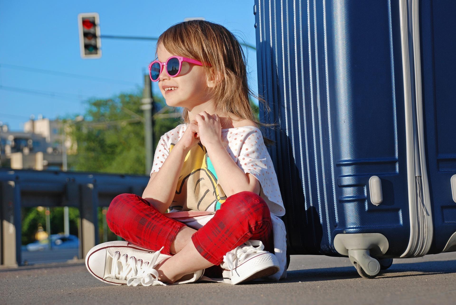 Co spakować ma wakacje z dzieckiem? Dziewczynka siedząca przy walizce,